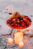 La vista del primo piano delle candele brillanti vicino alle ciliege ed alle pesche sul piatto Fotografia Stock Libera da Diritti