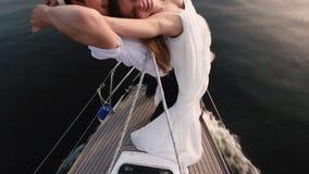 La vista del primo piano delle coppie felici che si tengono per mano e che stanno sulla prora della barca ai precedenti del mare archivi video