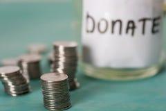 La vista del primo piano delle monete impilate ed il barattolo di vetro per donano Immagini Stock