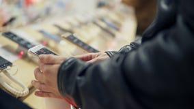 La vista del primo piano di un ` s del giovane passa la scelta del telefono cellulare nuovo in un negozio Sta provando come funzi archivi video