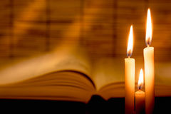 La vista del primo piano di vecchia candela bruciante con il vecchio libro vago sopra corteggia fotografie stock libere da diritti