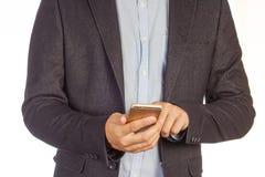 La vista del primo piano sull'uomo elegante in vestito utilizza lo smartphone isolato su fondo bianco immagine stock