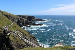 La vista del puente, las rocas y la agua de mar en Mizen dirigen Irlanda Fotos de archivo