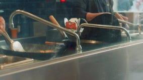 La vista del ` s dei cuochi passa la preparazione dell'alimento cinese in wok in ristorante nel mercato di boqueria video d archivio