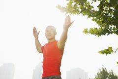 La vista delantera de joven, sonriendo, hombre muscular en una camisa roja que estira por un árbol, arma extendido en Pekín, China Foto de archivo libre de regalías
