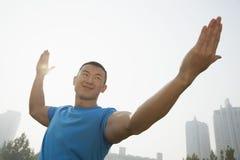 La vista delantera de joven, sonriendo, hombre muscular que estira, da extendido en Pekín, China Foto de archivo libre de regalías