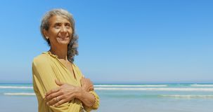 La vista delantera de la mujer afroamericana mayor activa feliz con los brazos cruzó la colocación en la playa 4k almacen de video