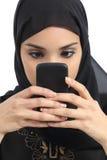 La vista delantera de una mujer árabe envició al teléfono elegante Imagen de archivo libre de regalías