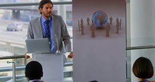 La vista delantera del altavoz masculino de Cuacasian habla en el seminario 4k del negocio metrajes