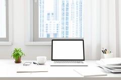 La vista delantera del workpark con la pantalla en blanco del ordenador portátil, el marco en blanco, y el cuaderno adentro modre Fotografía de archivo libre de regalías
