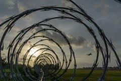 La vista dell'aeroporto dai recinti pungenti quando il sole va giù fotografia stock