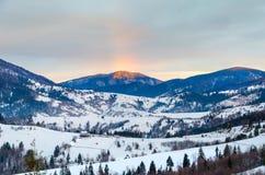 La vista dell'arcobaleno delle montagne fredde dell'inverno all'alba di legno recinta lo Sn Fotografie Stock Libere da Diritti