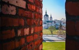 La vista della chiesa tramite un muro di mattoni Immagini Stock