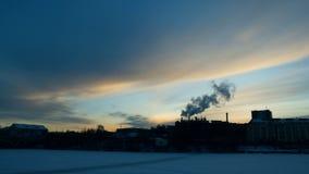 La vista della città di sera sopra cui pilota uno stormo degli uccelli nella distanza vicino e del fumo viene dai tubi del video d archivio