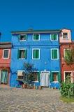 La vista della facciata variopinta della casa con il cespuglio fiorisce accanto alla porta in Burano immagini stock