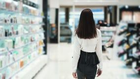 La vista della parte, donna va al deposito lungo gli scaffali, movimento lento dei cosmetici