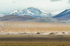 La vista delle montagne e la torre elettrica ad alta tensione allineano Fotografie Stock