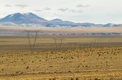 La vista delle montagne e la torre elettrica ad alta tensione allineano Fotografia Stock Libera da Diritti