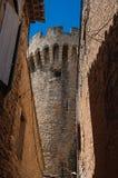 La vista delle pareti di pietra ed il castello si elevano in un vicolo stretto nel centro urbano storico di Gordes Fotografie Stock