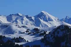La vista dello sci di Saanersloch pende e montagne innevate Fotografie Stock