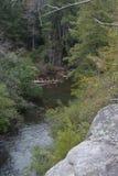 La vista desde el principio de un extremo del puente de balanceo en la caída de la cala de las caídas con los árboles caidos fotos de archivo