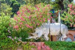 La vista di luce del giorno alla statua del rinoceronte ornated con i fiori fotografie stock libere da diritti