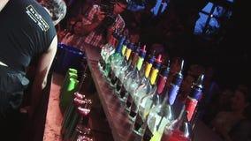 La vista di molte bottiglie differenti con le bevande resta sul supporto della barra in night-club esposizione intrattenimento video d archivio