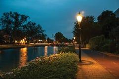 La vista di notte di ampio canale alberato, il ponte e la lampada inviano la luce nella priorità alta all'alba in Weesp Fotografie Stock Libere da Diritti