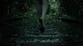 La vista di notte delle gambe fuggire ha spaventato la ragazza Ferrovia in foresta stock footage