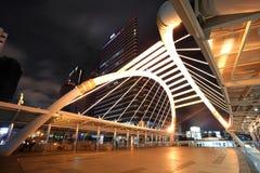 La vista di notte di alte costruzioni ed il cielo pubblico camminano Immagine Stock