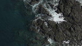 La vista di occhio dell'uccello tir indietroare delle onde di oceano che si schiantano su un litorale della roccia video d archivio