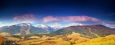 La vista di panorama di neve ha ricoperto i picchi di montagna in primavera Fotografia Stock