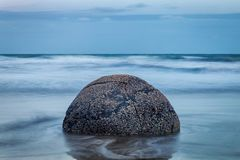 La vista di sera della pietra sferica perfetta ai massi di Moeraki tira fotografie stock libere da diritti