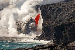 La vista diurna aérea de la porción superior de cascada formó flujo de lava roja del volcán en Hawaii que estallaba en el mar Imagen de archivo libre de regalías