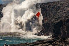La vista diurna aérea del top de la cascada formó flujo de lava roja del volcán en Hawaii que estallaba en el mar Foto de archivo libre de regalías