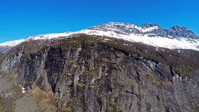 La vista frontale aerea della montagna del massiv con un'altra montagna dietro ha coperto in neve archivi video