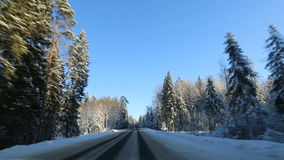 La vista frontale dall'automobile ha montato la macchina fotografica quando sentiero forestale nevoso dell'inverno di azionamento archivi video