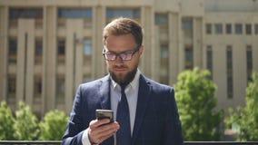 La vista frontale dell'uomo d'affari elegante sta utilizzando lo smartphone che sta sul fondo della costruzione della città archivi video