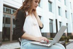 La vista frontale della studentessa è lavoro sulla tastiera del computer portatile sopra all'aperto a urbano Fotografie Stock Libere da Diritti