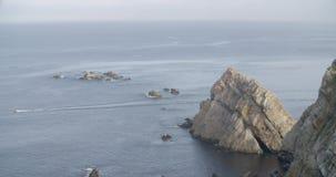 La vista general de una motora que cruza el mar con un grupo de rocas en ella está detrás almacen de metraje de vídeo