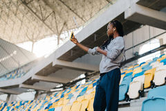 La vista horizontal del sportgirl afroamericano serio que toma el selfie en el estadio Fotografía de archivo libre de regalías