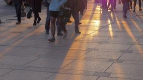 La vista inferior de las piernas de la gente contra puesta del sol irradia en la piedra de pavimentación almacen de metraje de vídeo