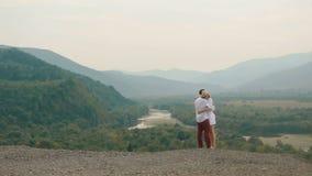 La vista integral de los pares cariñosos de abrazo alegres que se colocan en el borde de las montañas opinión del abejón metrajes