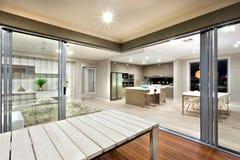 La vista interna dell'luci di sala moderne ha acceso con la tavola di legno Immagini Stock