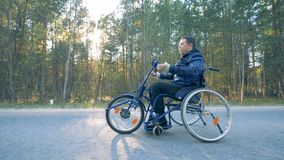 La vista lateral de conseguir de la silla de ruedas del entrenamiento se movió por una persona discapacitada con sus brazos metrajes