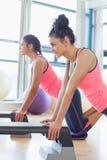 La vista lateral de dos mujeres aptas que realizan aeróbicos del paso ejercita Imagenes de archivo