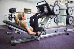 La vista lateral de la mujer del ajuste que hace la pierna clava el gimnasio Imagen de archivo