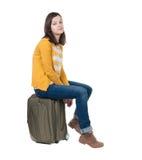 La vista lateral de la mujer que camina en rebeca se sienta en una maleta Foto de archivo