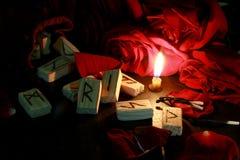 La vista lateral de las runas de madera, alrededor es los pétalos de rosas rojas, una vela está quemando siguiente Detrás de las  imagenes de archivo