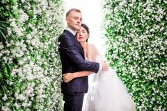 La vista lateral de los pares románticos de la boda con los ojos cerró el abarcamiento en medio de decoraciones de la flor Fotografía de archivo
